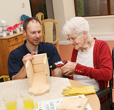 A resident from The Grove Care Home constructing a bird box.
